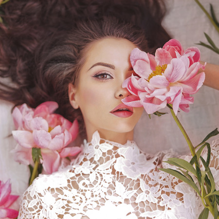 Photo pour Stylish fashion photo of beautiful young woman lies among peonies. Holidays and Events. Valentine's Day. Spring blossom. Summer season - image libre de droit