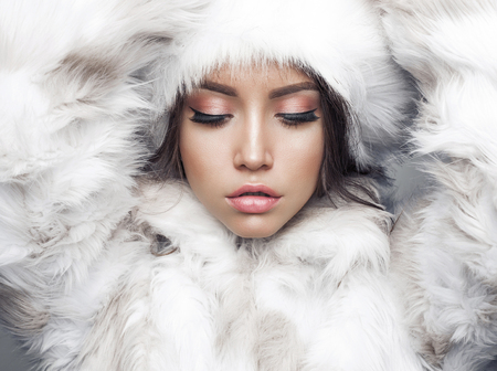 Photo pour Fashion studio portrait of beautiful lady in white fur coat and fur hat. Winter beauty in luxury. Fashion fur. Beautiful woman in luxury fur coat. Fashion model posing in eco-fur coat and eco-fur hat - image libre de droit