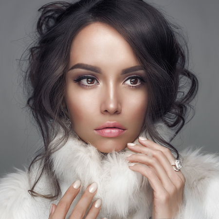 Photo for Fashion studio portrait of beautiful lady with elegant hairstyle in white fur coat. Winter beauty in luxury. Fashion fur. Beautiful woman in luxury fur coat. Fashion model posing in eco-fur coat - Royalty Free Image