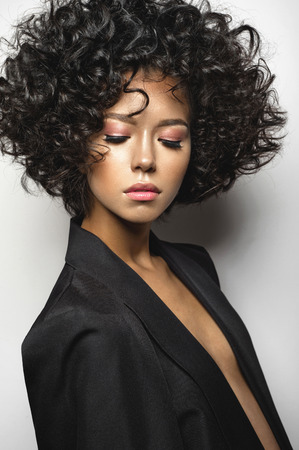 Photo pour Fashion studio portrait of beautiful woman in black cape with afro curls hairstyle. Fashion and beauty - image libre de droit
