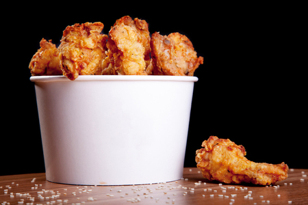 Photo for BBQ Chicken wings in a white bucket on a wooden table and black background. - Royalty Free Image