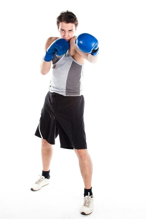 A young boxer in gray shirt and blue boxing gloves