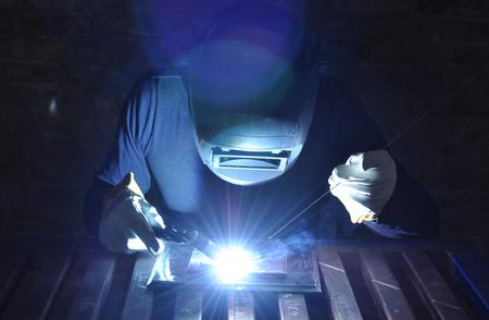 Foto de welder welds metal using tig with black background - Imagen libre de derechos