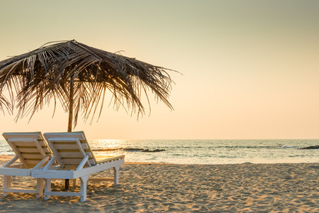 Foto de empty chairs under thatched umbrellas on a sandy beach - Imagen libre de derechos