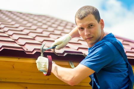 Photo pour Portrait of a male repairman engaged in repairing a roof of a house, a portrait against a tile - image libre de droit