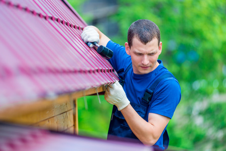 Photo for a man with a hammer repairs the roof of a house, shooting outdoors - Royalty Free Image