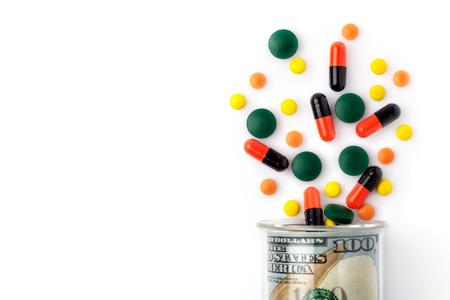 Foto de Colorful pills spilled from a bottle made of money, on white background. The Concept of Drug Purchase. - Imagen libre de derechos