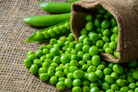 Photo pour hearthy fresh green peas and pods on rustic fabric background - image libre de droit