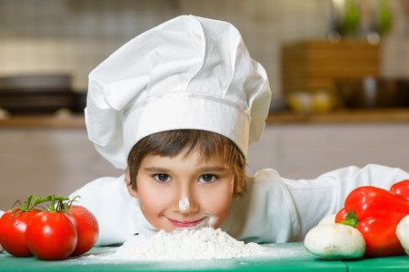 Foto de Funny happy chef boy cooking at restaurant kitchen and bent over the flour. - Imagen libre de derechos