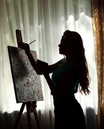 Photo pour Silhouette woman artist draws paint picture on easel, backlight portrait indoor - image libre de droit