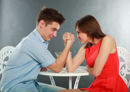 Foto de Young happy couple challenge fighting in arm-wrestling at table, in studio isolated on gray - Imagen libre de derechos