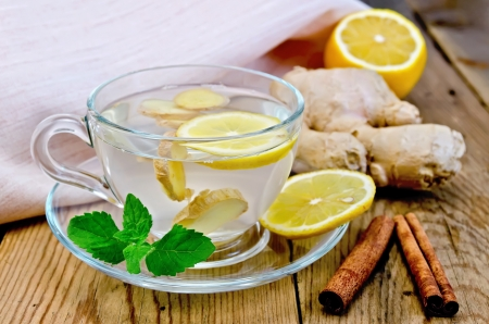 Photo for Ginger tea in a glass cup, lemon, cinnamon, ginger, mint, napkin against a wooden board - Royalty Free Image