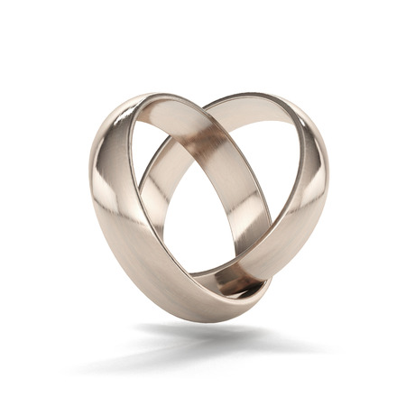 Foto de couple of gold wedding rings in heart shape isolated on a white background - Imagen libre de derechos