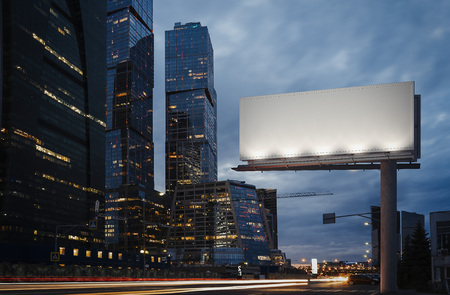 Foto de Blank billboard at twilight next to skyscrapers. 3d rendering - Imagen libre de derechos