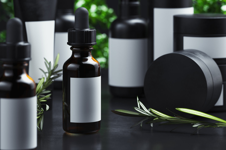 Foto de Cosmetic Bottle with olive oil, cream, gel or lotion. Beauty product package, blank template of glass container in black cardboard packages next to Olive tree branch on dark background. 3d rendering. - Imagen libre de derechos