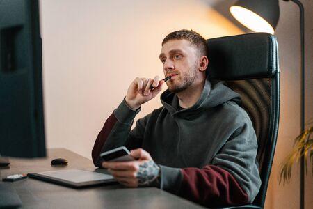 Foto für Young attractive man working on Graphics tablet. Modern working place of designer, painter, photographer. - Lizenzfreies Bild