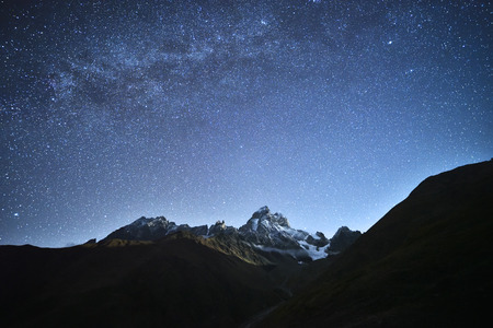 Photo pour Night landscape. Starry sky with the Milky Way over the mountains. Mount Ushba in the light of the rising moon. Main Caucasian ridge. Zemo Svaneti, Georgia - image libre de droit
