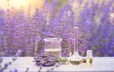 Photo pour Essential lavender oil in the bottle with dropper on the gray wooden desk. Horizontal close-up. - image libre de droit