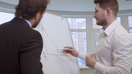 Attractive young businessman drawing on the flip chart. Handsome bearded man in white shirt explaining something to his partner. Middle aged caucasian male manager in suite listening to his colleague at the office