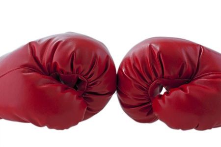 Red boxe gloves fronting each other over white background