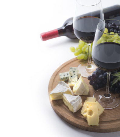 Photo pour Two glasses of red wine, bottle, cheese and grapes on white background - image libre de droit