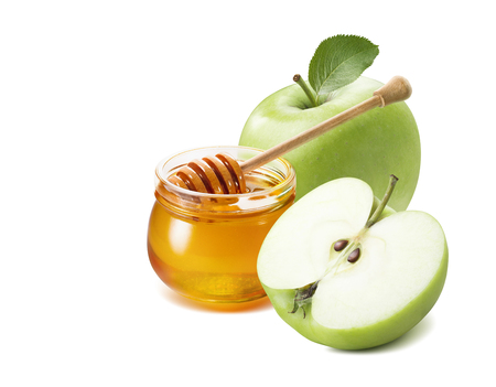 Foto de Green apple half and honey jar for Jewish New Year isolated on white background for poster design - Imagen libre de derechos