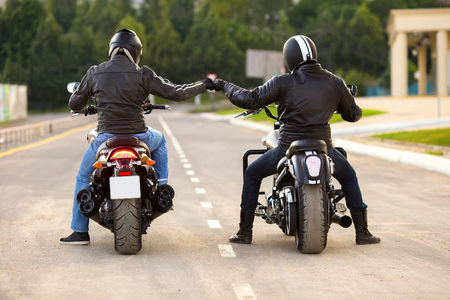 Foto de Two bikers ot motocycles handshaking with knuckle on road - Imagen libre de derechos