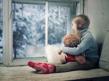 Photo pour Little girl looking out the window. Outside, the winter snow. - image libre de droit
