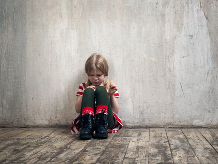 Photo pour Sad little girl sitting on the floor. The concept of child psychology, loneliness, resentment - image libre de droit