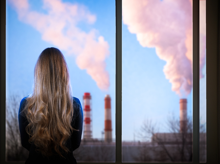 Photo for The girl looks through the window at the district heating pipe. Concept - ecology of the city, environment, harmful emissions into the atmosphere - Royalty Free Image