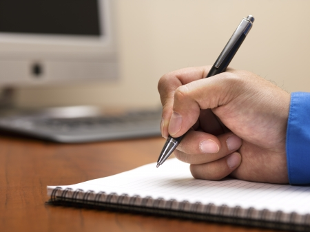 Detailed shot of human hand writing with pen on spiral writing pad on wooden office desk.