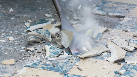 Photo pour Removal of old floor during a renovation of housing. Idea of manual work. Close-up of a chisel from demolition hammer, fragments of ceramic tiles, dust and small sparks. - image libre de droit