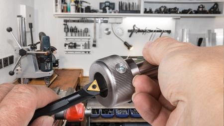 Foto de Detail of tool bit and metallic bolt in workman's hands. Handy man's workshop with a drill, a vice and various tools in the background. Idea of engineering and industry. - Imagen libre de derechos