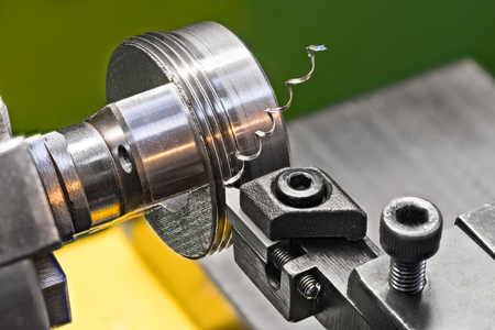 Foto de Threading by a steel tool bit on a lathe. Close-up of turning a rotating metallic workpiece clamped in a chuck jaws of the machine tool. Beautiful twisted swarf. Idea of machining and metalwork. - Imagen libre de derechos