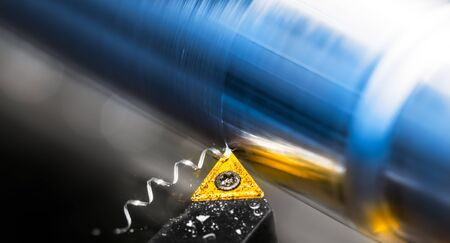 Foto de Yellow lathe tool bit detail working on metal product with reflection on shiny surface. Turning of silvery-blue workpiece with beautiful motion blur. Screwed swarf and white bokeh on black background. - Imagen libre de derechos