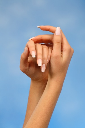 close-ups of the hands of a young woman with long white nails nail against a blue background