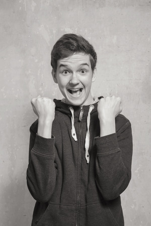 Photo for Black and white portrait  of a young man with a gesture expressing strong joy. Studio photography. - Royalty Free Image