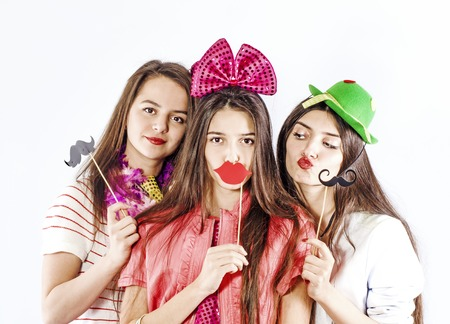 Photo pour young smiling three girls holding near the face of paper props in the form of lips, mustaches for the photo, isolated on white background - image libre de droit