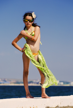Photo pour Attractive brunette teenage girl in effective attire posing on the beach by the sea or ocean - image libre de droit