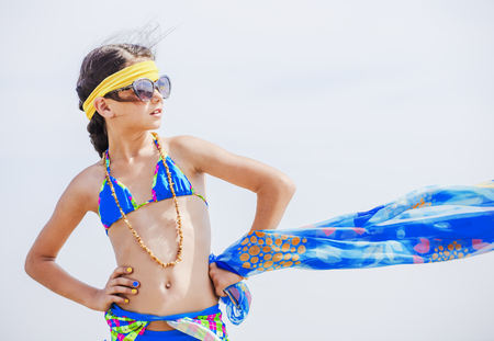 Funny young girl in a swimsuit against the sky