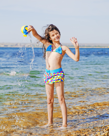 Photo for A cool young girl in a swimsuit with long hair flying in the wind watering from a watering can standing in sea water - Royalty Free Image
