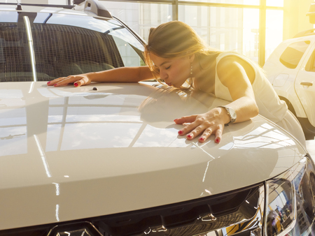 Photo for Dream about car. Gorgeous smiling woman kissing hood of new white car in the dealership. - Royalty Free Image