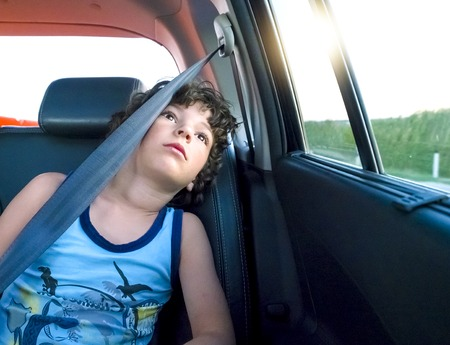 A little boy is sitting in the back wearing a seatbelt patiently in the back of a car and is dreamily looking out the window. Traveling with children concept