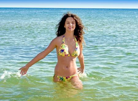 Foto de Charming girl having fun on the seashore. girl in summer swimsuit at sea - Imagen libre de derechos