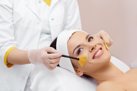 Foto de Cosmetology. Spa clinic. Beautiful woman at facial treatment procedure. Young healthy skin. Facial mask. Skin rejuvenation. - Imagen libre de derechos