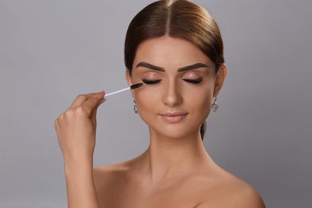 Mascara. Beauty Makeup, Fresh Soft Skin And Long Black Thick Eyelashes Applying Mascara With Cosmetic Brush. Eyelashes extensions. Fake Eyelashes.