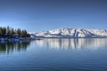 A reflection of Elk Point on Lake Tahoe from Marla Bay with Pyramid Peak and Mount Price reflecting in the background.
