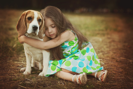 Photo pour little girl is holding dog outdoors - image libre de droit