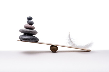 Foto de Stone balance with plume. Concept of heavy and light. - Imagen libre de derechos