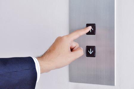 Photo pour Businessman hand touching going up sign on lift control panel - image libre de droit
